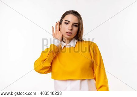 A Hard Of Hearing Young Beautiful Woman Putting Her Hand To Ear And Listens. The Concept Of Secrecy,