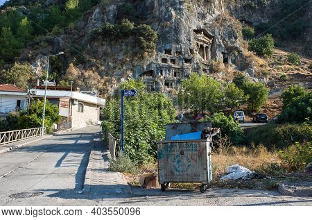 Fethiye, Turkey - 29 September, 2019: Cat sits on big trash can by the road with view of Ancient Lycian Rock Tombs on mountain clif on backdrop