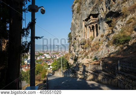 Fethiye, Turkey - 29 September, 2019: Ancient Lycian Rock Tombs on mountain cliff, cctv camera on pole across the street, view of Fethiye town from the hill