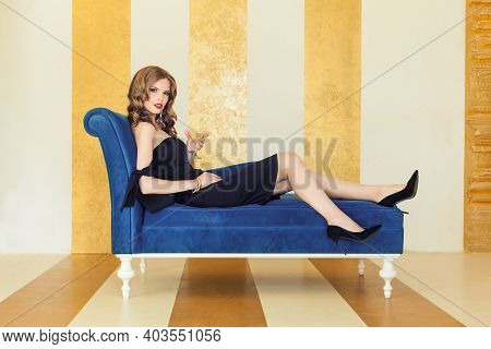 Beautiful Sensual Woman In Black Cocktail Dress Holding Wine Glass Sitting On Sofa In Luxurious Inte