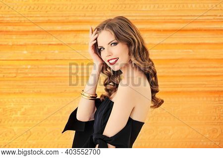 Cheerful Model Woman With Curly Hair And Makeup On Gold Background