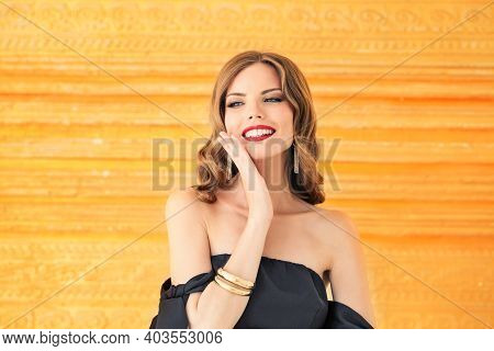 Happy Young Woman With Makeup, Curly Hair And Cute Smile On Gold Background