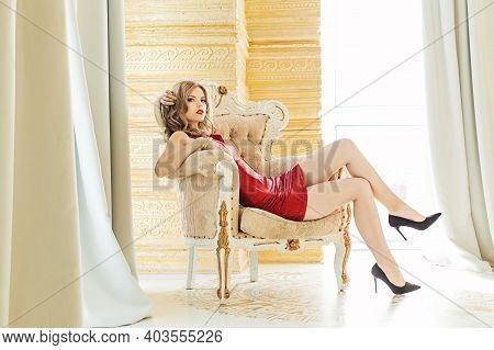 Young Woman Sitting In Retro Armchair In Luxurious Interior