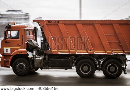 Moscow, Russia - January 15, 2021: Orange Truck Is Running On The Street In City. Recycling Truck Ri