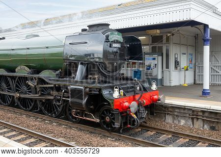 Queensferry, Scotland - May 20, 2018: Flying Scotsman Steam Train Passing Station Dalmeny In Queensf