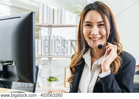 Smiling Friendly Asian Female Call-center Agent With Headset Working On Support Hotline In The Offic