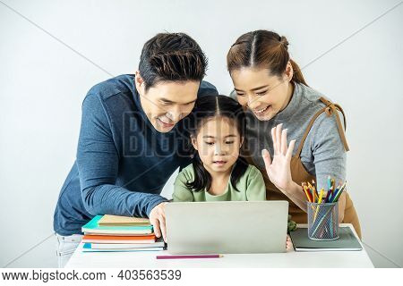 Happy Young Mother And Father And Little Daughter Making Video Call With Laptop Computer, Gesturing