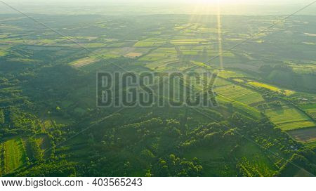 Sunshine Bokeh Above Green Haze Hilly Landscape, Several Cultivated Plots Among Forest Trees In Earl