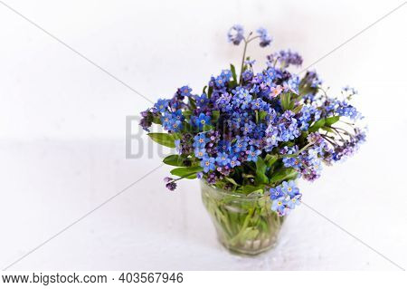 Blue Wildflowers In A Glass Cup Against A White Wall. White Background. Forget Me Nots.