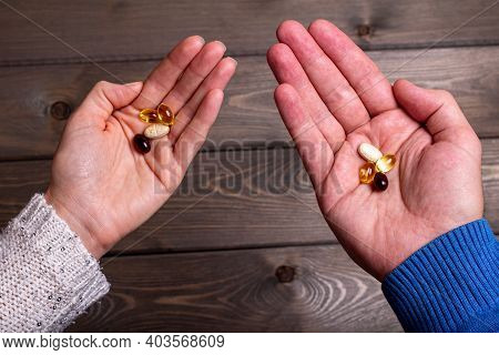 A Man And A Woman Hold Vitamins In Their Hands On A Blurry Wooden Background. Vitamin Capsules On Th