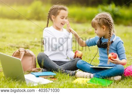 Cute Schoolgirls Eat Outdoors. Healthy Lunches For Schoolchildren. Lunch Box With Fruit. School Lunc