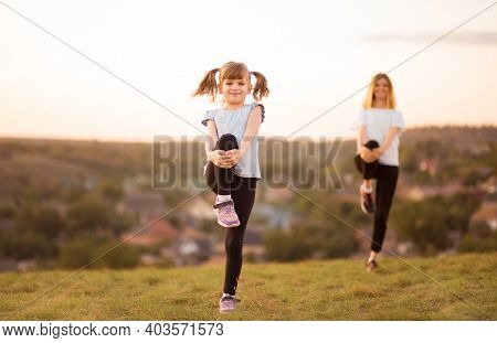 Sporty Mother And Daughter. Woman And Child Training In The Park. Outdoor Sports. Healthy Sport Life