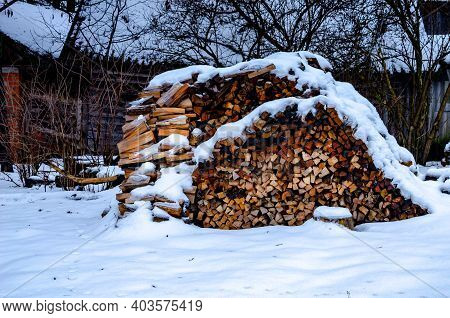 Pile Of Firewood In Winter. Many Chopped Logs. A Pile Of Chopped Firewood, Prepared For Winter. Sawe
