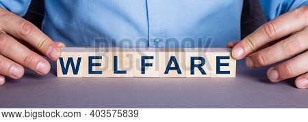 The Word Welfare Is Made Up Of Wooden Cubes By A Man. Business Concept