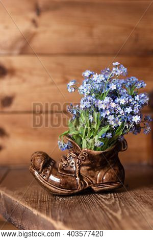 Bouquet Forget Me Not Flowers In A Ceramic Vase On A Wooden Background.