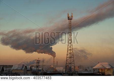 Smoke rises from the chimney of the boiler room over the city and the cell tower is in the foreground. Russia, Novosibirsk region, air temperature -41 degrees Celsius