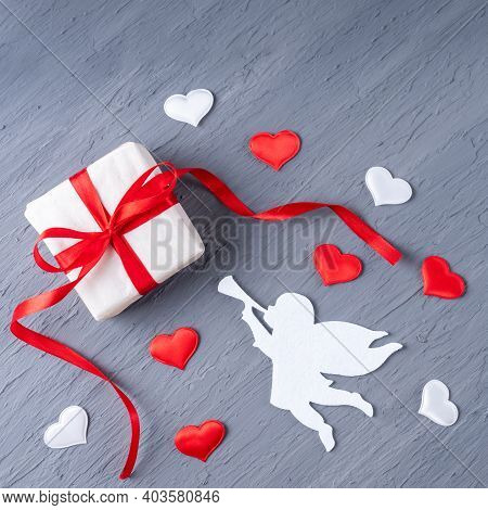 Gift In White Paper With A Red Ribbon, An Angel Playing The Trumpet, White And Red Heart Shape On A