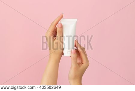 Young Female Hands Holding Blank White Plastic Cosmetic Tube On Pink Background. Mock-up Of Packagin
