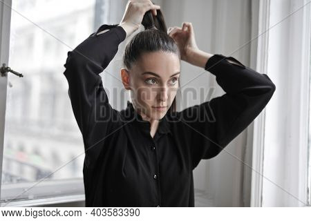 young woman puts her hair back