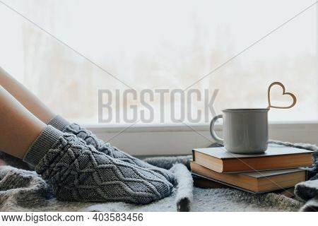Cozy Winter Still Life: Woman Legs In Warm Woolen Socks Under Shaggy Blanket And Mug Of Hot Beverage