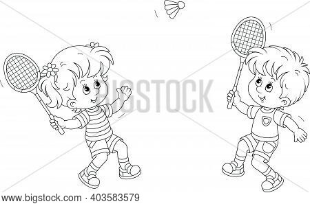 Happy Little Kids Playing Badminton With Rackets And A Flying Shuttlecock In A Fun Game On A Summer
