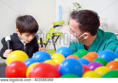 Physical Therapist Playing With Children, With Cerebral Palsy. High Quality Photo