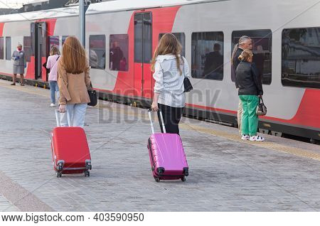 Petrozavodsk, Russia - August 21th, 2020: People On The Rail Station. Two Girls With Their Luggage G