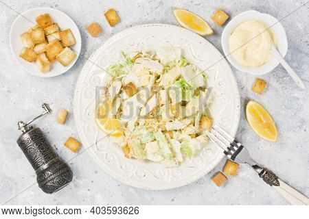 Caesar Salad With Chicken, Lettuce, Parmesan Cheese, Crouton And Mayonnaise Sauce In Plate On Gray C