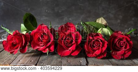 Red Roses In A Row On Dark Wooden Boards. Horizontal Background For Valentine's Day Greeting Card Wi