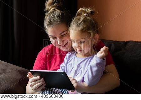 Mother And Daughter At Home Use Tablet Pc. Motherhood, Spending Time With A Child. Parental Love.