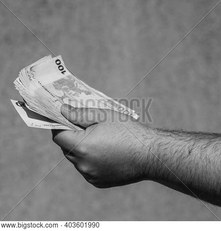 Hand Holding And Showing Euro Money Or Giving Money. World Money Concept, 100 Euro Banknotes Eur Cur