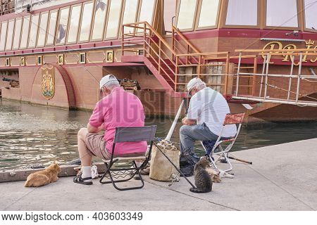 Sevastopol, Russia - January 7, 2020: Two Male Fishermen In Casual Clothes Sit On Folding Chairs On