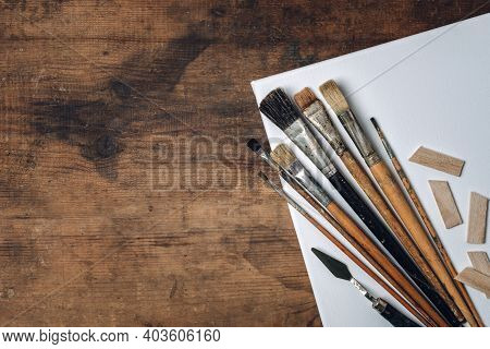 Artistic Tools On Old Dark Wooden Table. Set Brushes For Oil Painting, Palette Knives, Roll Of Paper