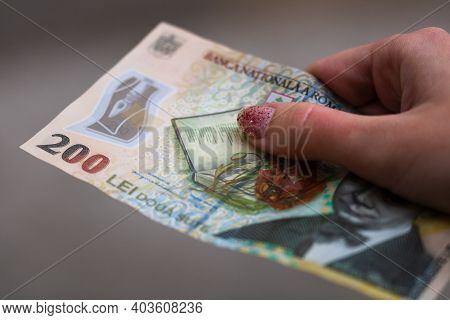 Girl Hands Giving Money. Holding Lei Banknotes On A Blurred Background, Romanian Currency