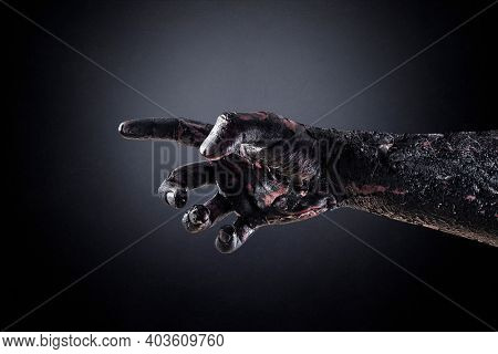 Creepy zombie hand over dark background with clipping path