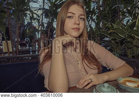 Heartbroken Lady Sitting In Cafeteria. She Is Looking Sad And Melancholic. Angle View.