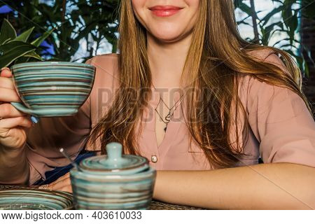 Partial View Of Lady Holding Cup Of Coffee In Hands In Cafeteria