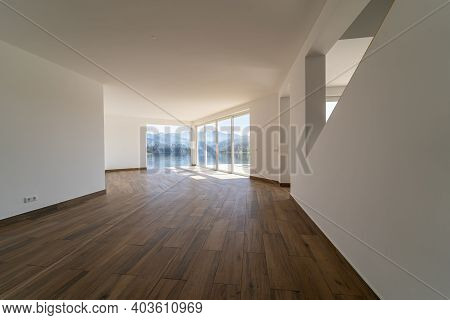 Empty Room With Dark Wooden Floating Laminate Flooring. House Interior, Wide Bedroom Space. New  Hou