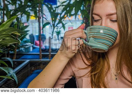 Sad Lovesick Lady Is Posin Sitting In Cafe. There Are Coffee Cup And Sugar Bowl In Front Of Her. She