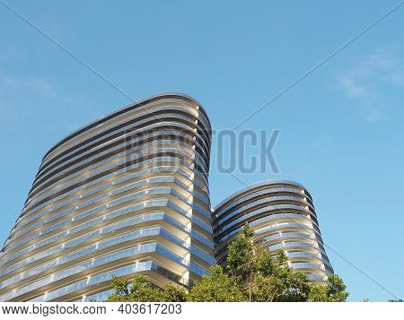 Russia, Sochi 05.07.2020. Two Highrise New Buildings Of An Unusual Oval Shape Against A Blue Sky