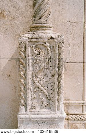 Stone Wall With A Flower-shaped Bas-relief On A Column.