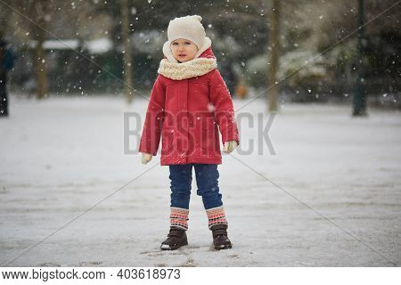 Unhappy Toddler Girl On A Day With Heavy Snowfall. Little Child Uncomfortable With Cold Weather And