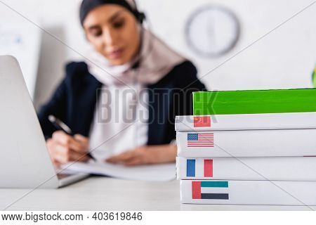 Selective Focus Of Dictionaries Of Foreign Languages Near Arabian Translator Working On Blurred Back