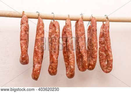 Drying Sausages From Raw Minced Meat In Limbo On A Wooden Stick On A White Wall Background At Home.