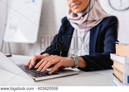 Cropped View Of Smiling Arabian Translator Typing On Laptop Near Dictionaries Of Foreign Languages,