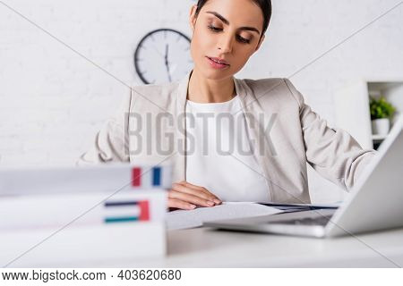 Focused Translator Working Near Laptop And Dictionaries Of French And Arabian Languages On Blurred F