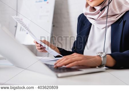 Cropped View Of Arabian Interpreter Typing On Laptop While Translating Document, Blurred Foreground