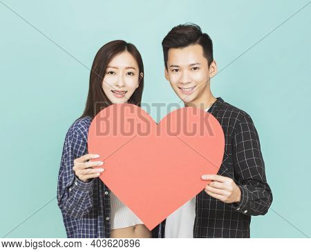 Young Couple Holding Red Heart Together Standing Over Blue Background
