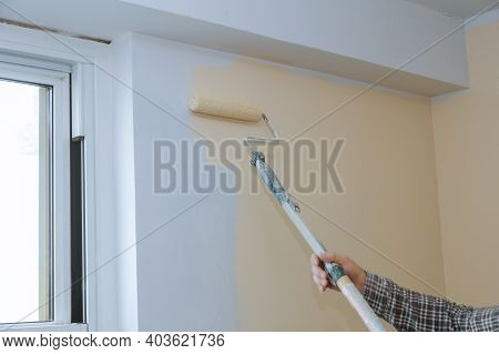 Rear View Of Painter Paints The Wall With A Roller In Room