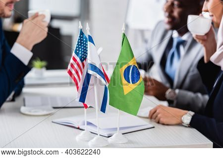 Selective Focus Of American, Brazilian And Israeli Flags Near Interracial Business Partners Drinking